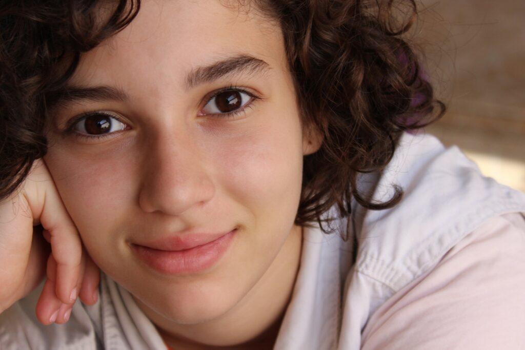 Έφηβο κορίτσι χαμογελά με αίσθημα γαλήνης