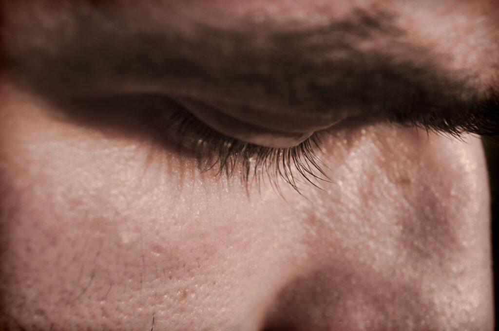Άνδρας κλείνει τα μάτια προβληματισμένος και γέρνει το κεφάλι προς τα κάτω