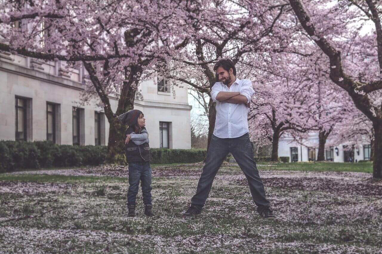 Πατέρας και παιδί παίζουν μαζί σην αυλή με τις ανθισμένες αμυγδαλιές