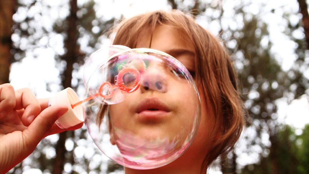 Μικρό κορίτσι φυσάει μπουρμπουλήθρες στο πάρκο