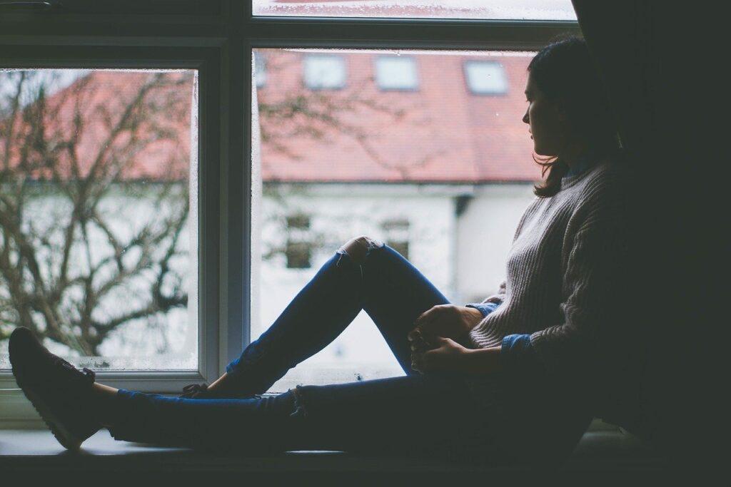 Νεαρή γυναίκα κοιτάει μελαγχολικά πίσω από το παράθυρο και σκέφτεται ότι θέλει να αλλάξει δουλειά