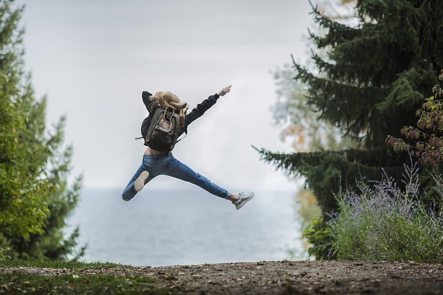 Κορίτσι πηδά ευτυχισμένο σε έναν δρόμο ανοιχτό επειδή συμπλήρωσε σωστά το μηχανογραφικό της δελτίο